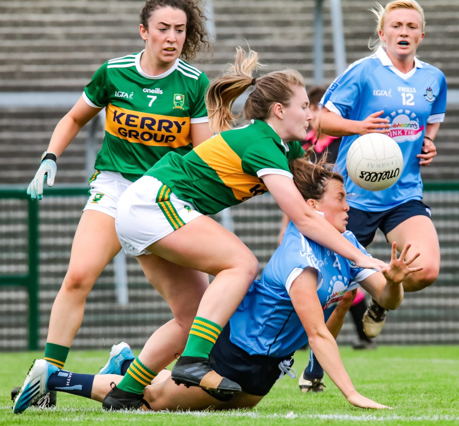 Dublin Ladies footballer in a sky blue jersey and navy shorts is fouled by a Kerry player in a green jersey and white shorts