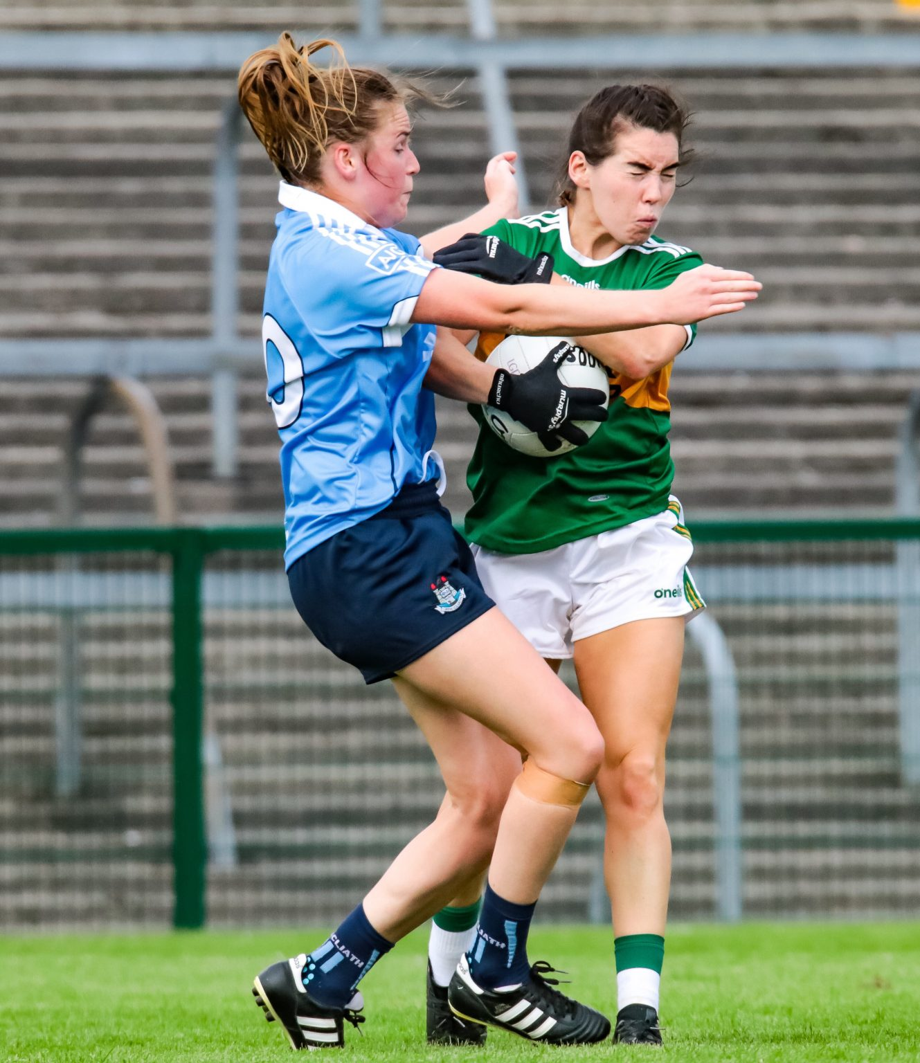 Dublin player in a sky blue jersey and navy shorts tackles a Kerry player in a green and gold jersey and white shorts, photo used to promote the Dublin LGFA notes which include Goal Keeping Workshop Info