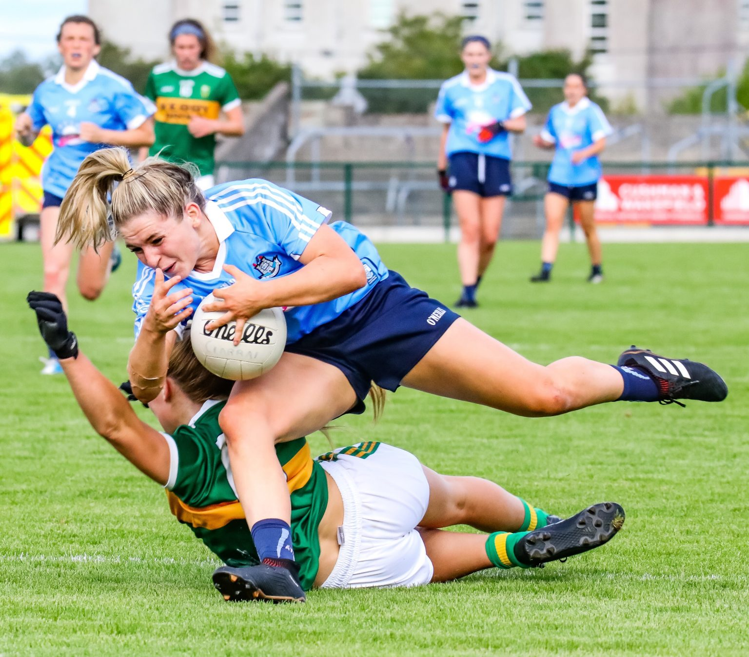 Dublin Ladies footballer in sky blue jersey and navy shorts falls over a Kerry player in green jersey and white shorts as the reigning champions Dublin beat Kerry in the quarter final
