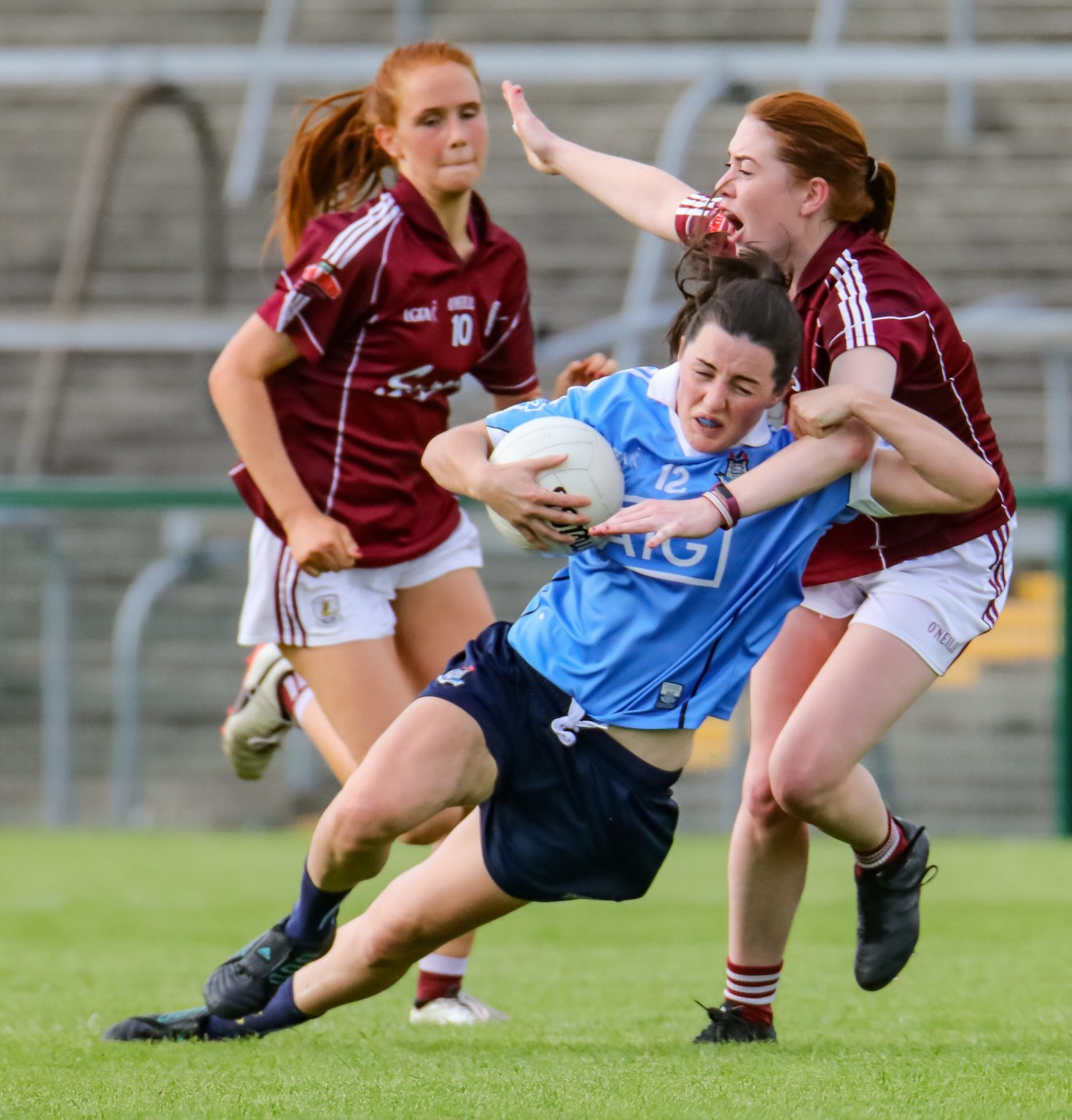 Dublin Ladies footballer in a sky blue jersey and navy shorts is fouled by a Galway player in a maroon jersey and white shorts Dublin won the game and qualified for their fifth straight TG4 All Ireland final