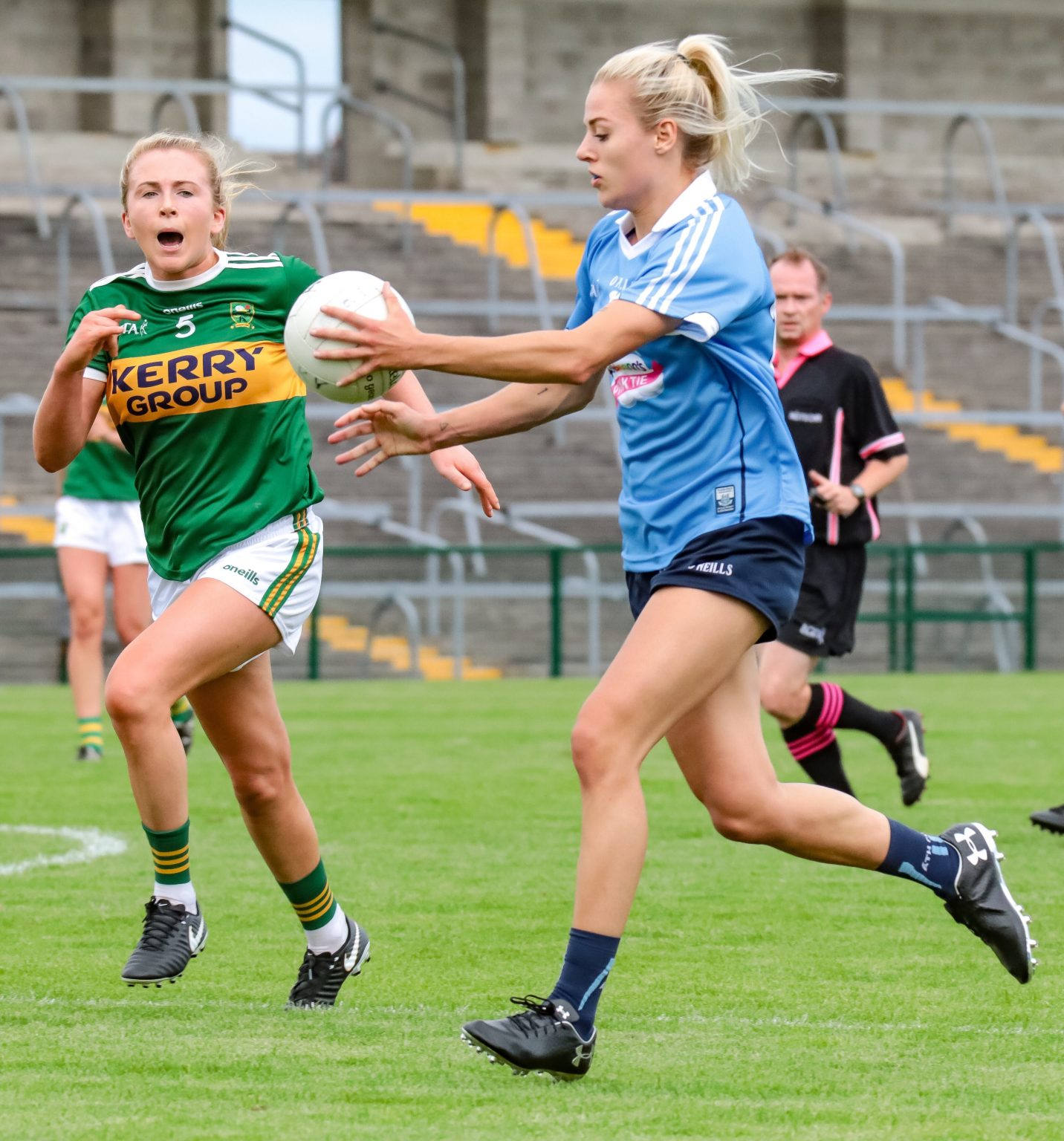 A Dublin Ladies footballer in a sky blue jersey and navy shorts runs at the Kerry defence