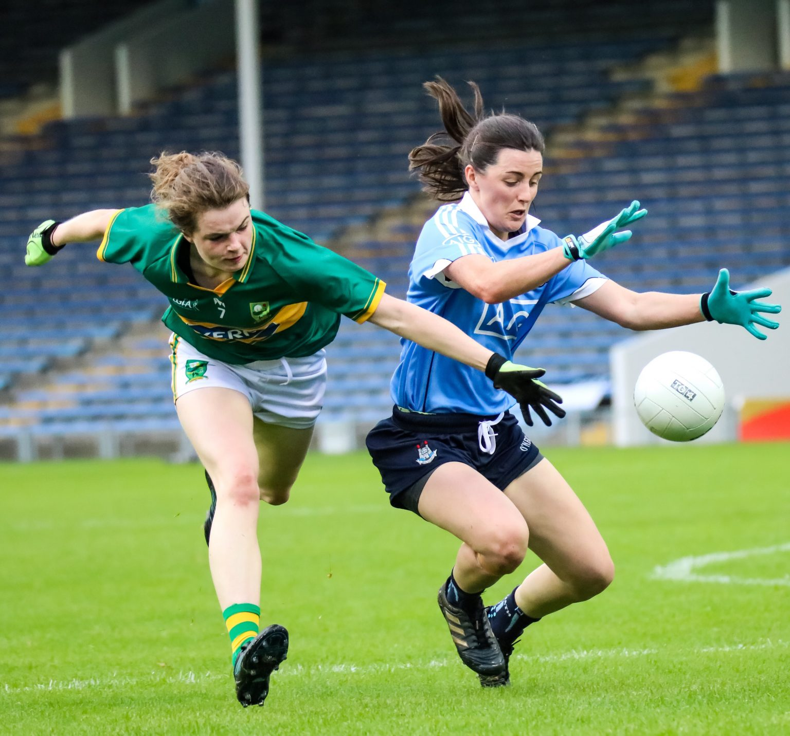 A dublin player in sky blue jersey and navy shorts and a Kerry player in a green and gold jersey battle for the ball in the All Ireland Senior Ladies Football championship