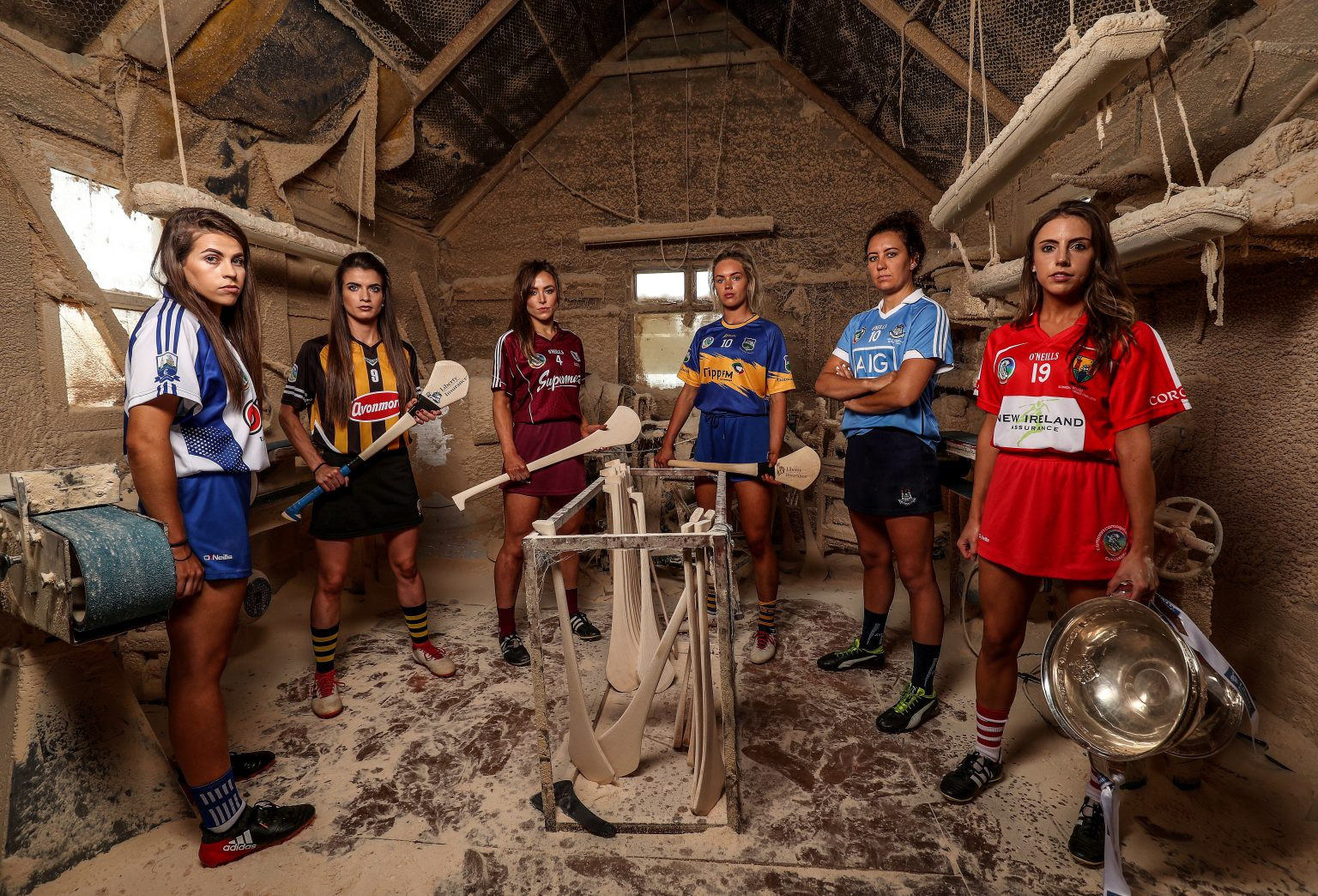 Six Camogie Players from the remaining Senior Championship contenders in a Hurley making shed