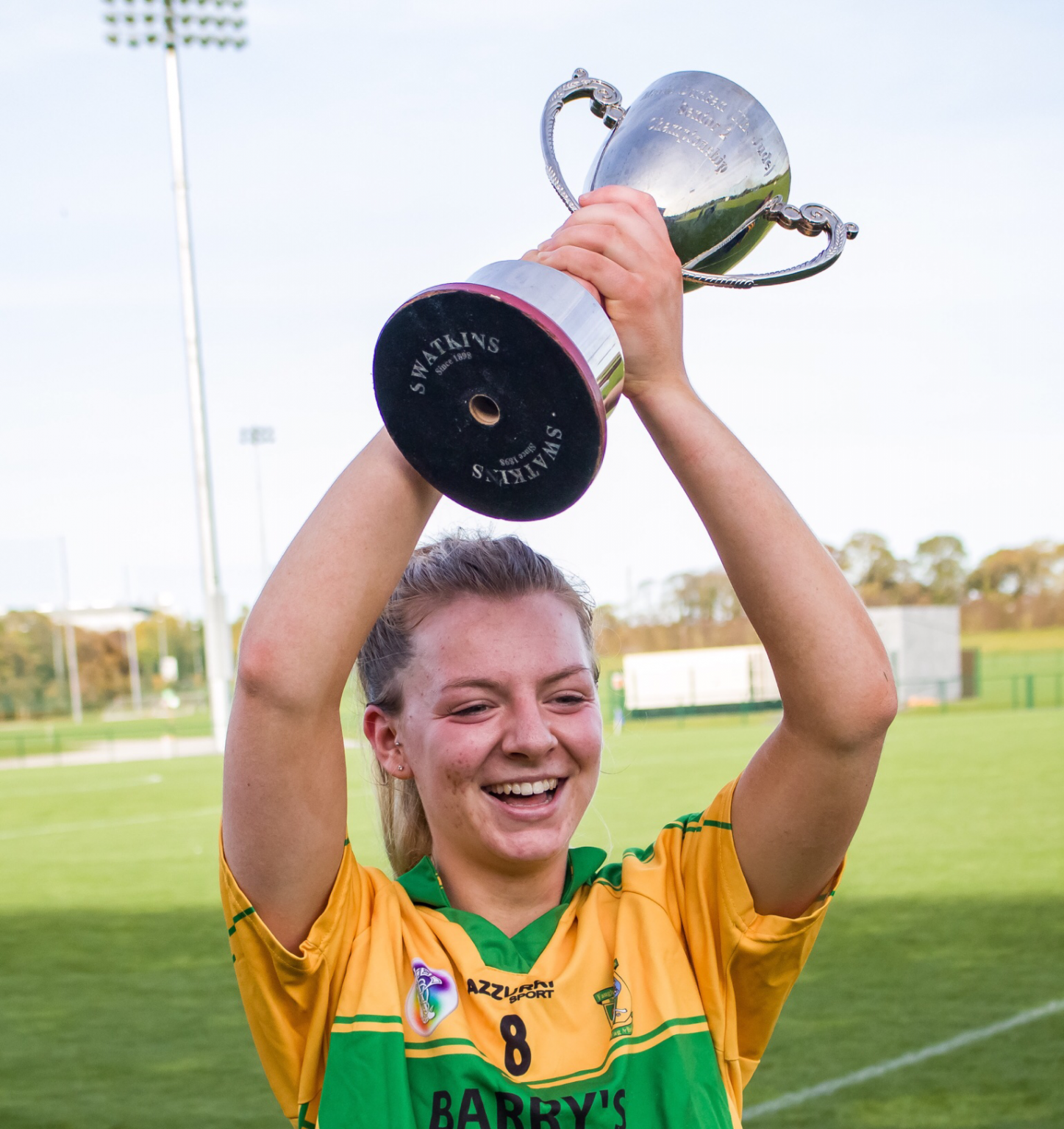 Faughs Captain In A Yellow Jersey with green stripe across the chest raises the Senior 2 title above her head