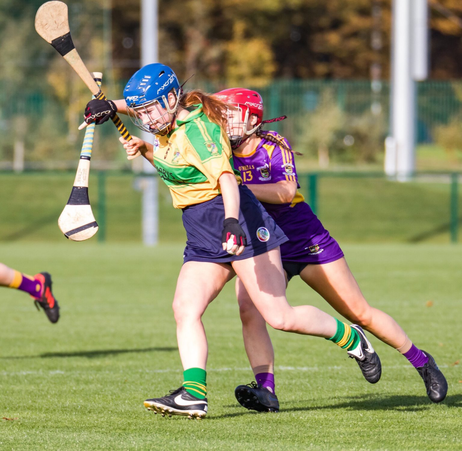 Faughs Celtic Camogie Player in a yellow and green jersey tries to escape the tackle of a Kilmacud player in purple and gold jersey