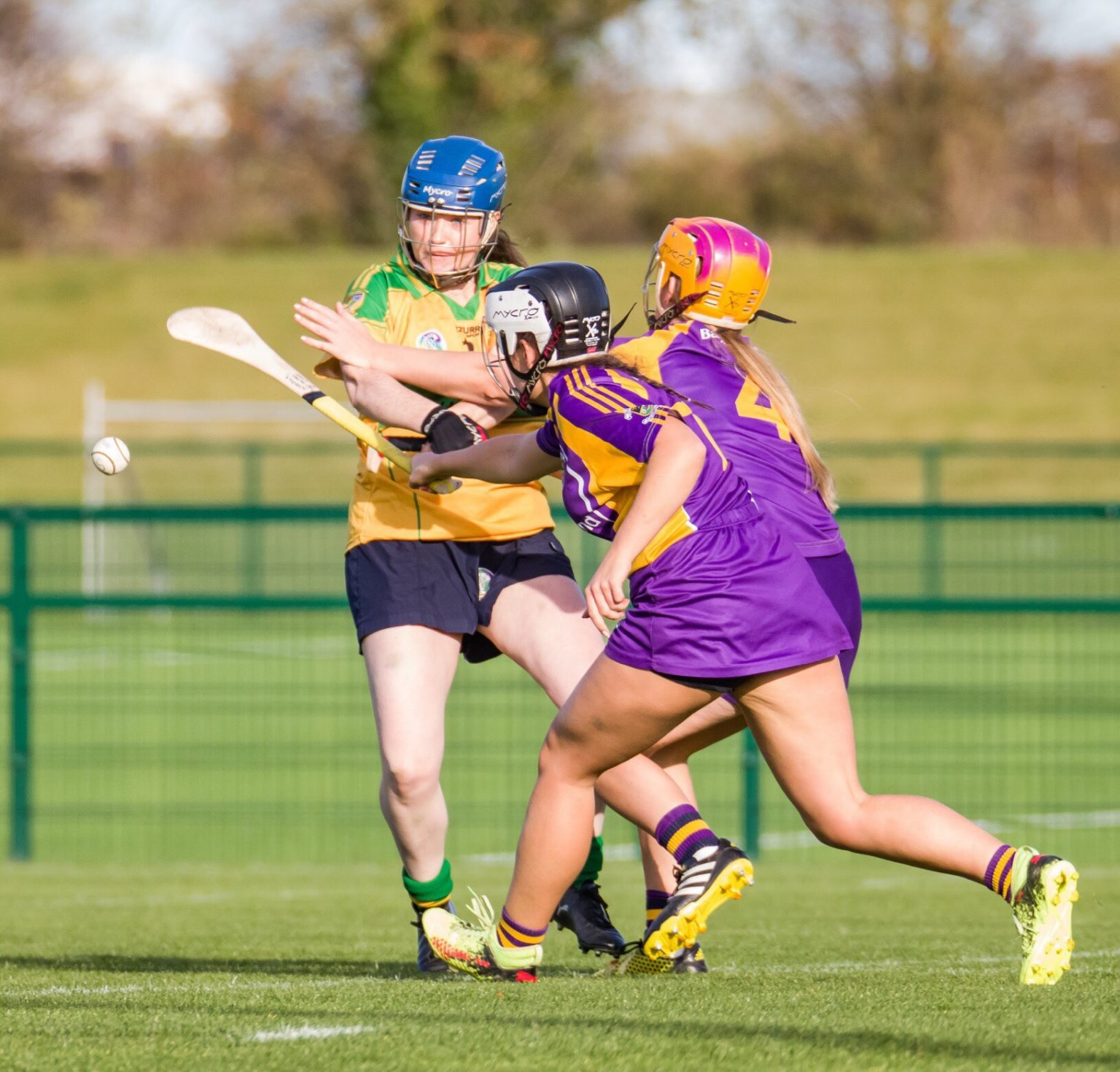 Two Kilmacud Crokes Players In purple and gold jerseys try to block the shot of a Faughs Celtic player in yellow and green jersey during the senior 2 final