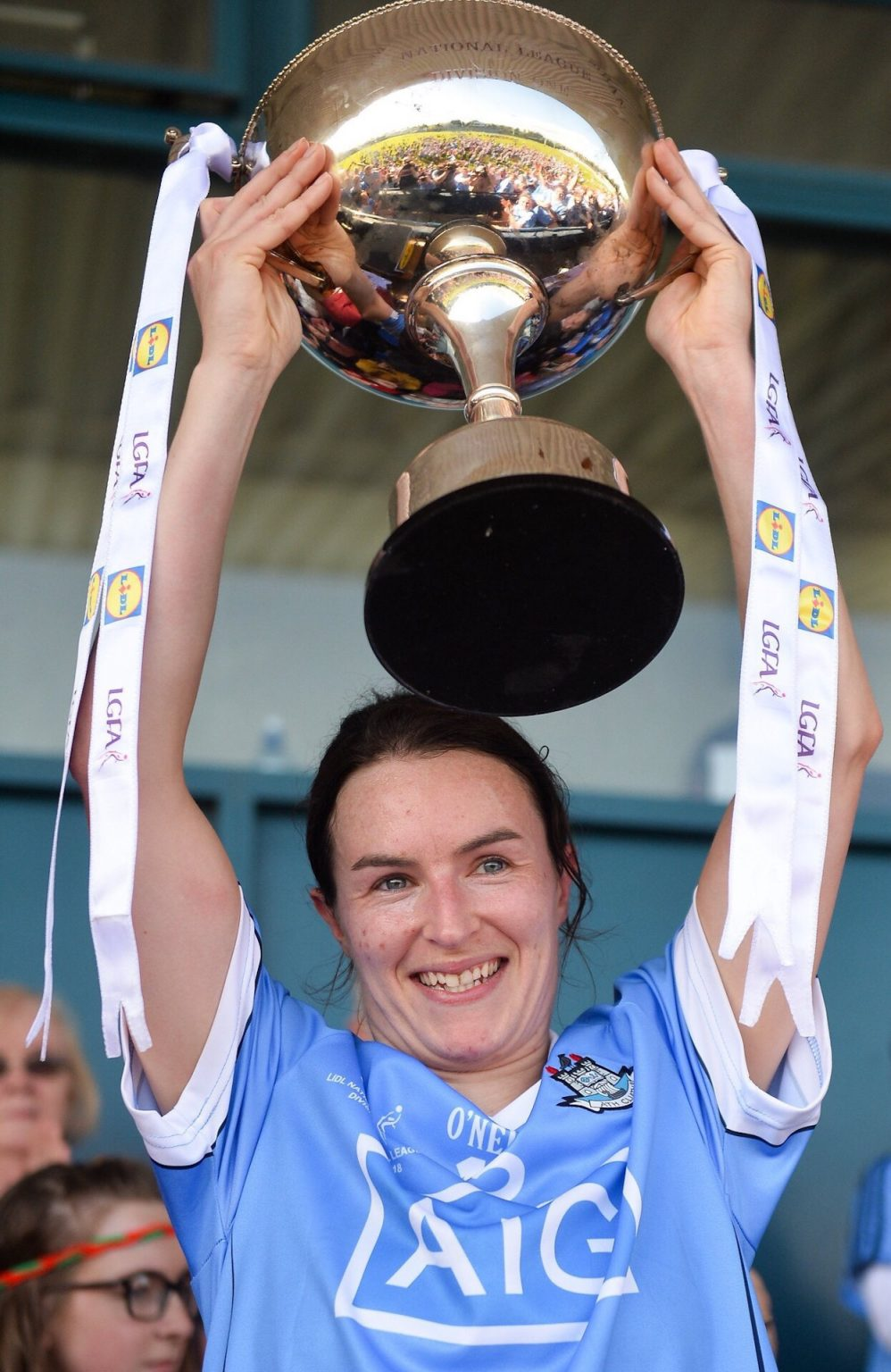 Dublin Captain Sinead Aherne In a sky blue jersey raises the Lidl NFL Division 1 Trophy above her head, dublin start defence against donegal as Lidl NFL Fixtures announced for 2019