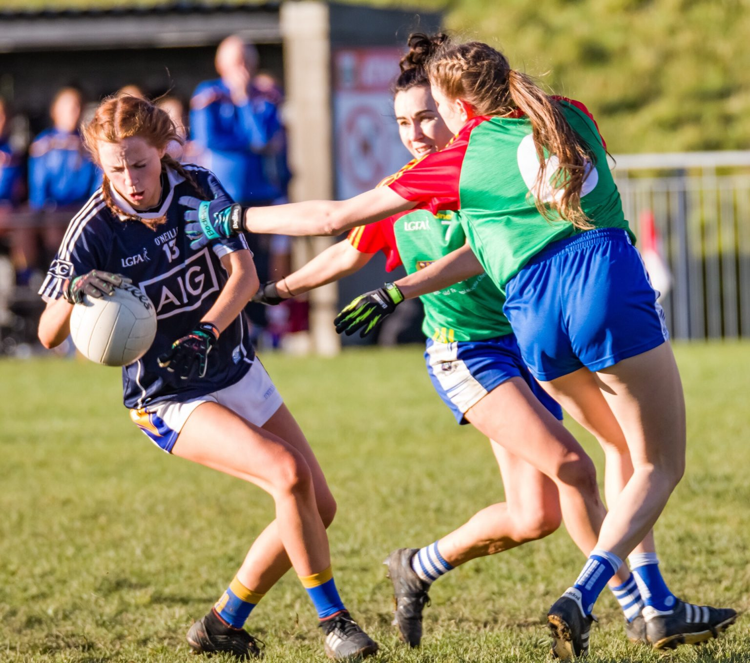 Castleknock Ladies footballer in a navy jersey and white shorts evades the attention of two opponents in green jerseys with red sleeves in the Junior Club Championship final