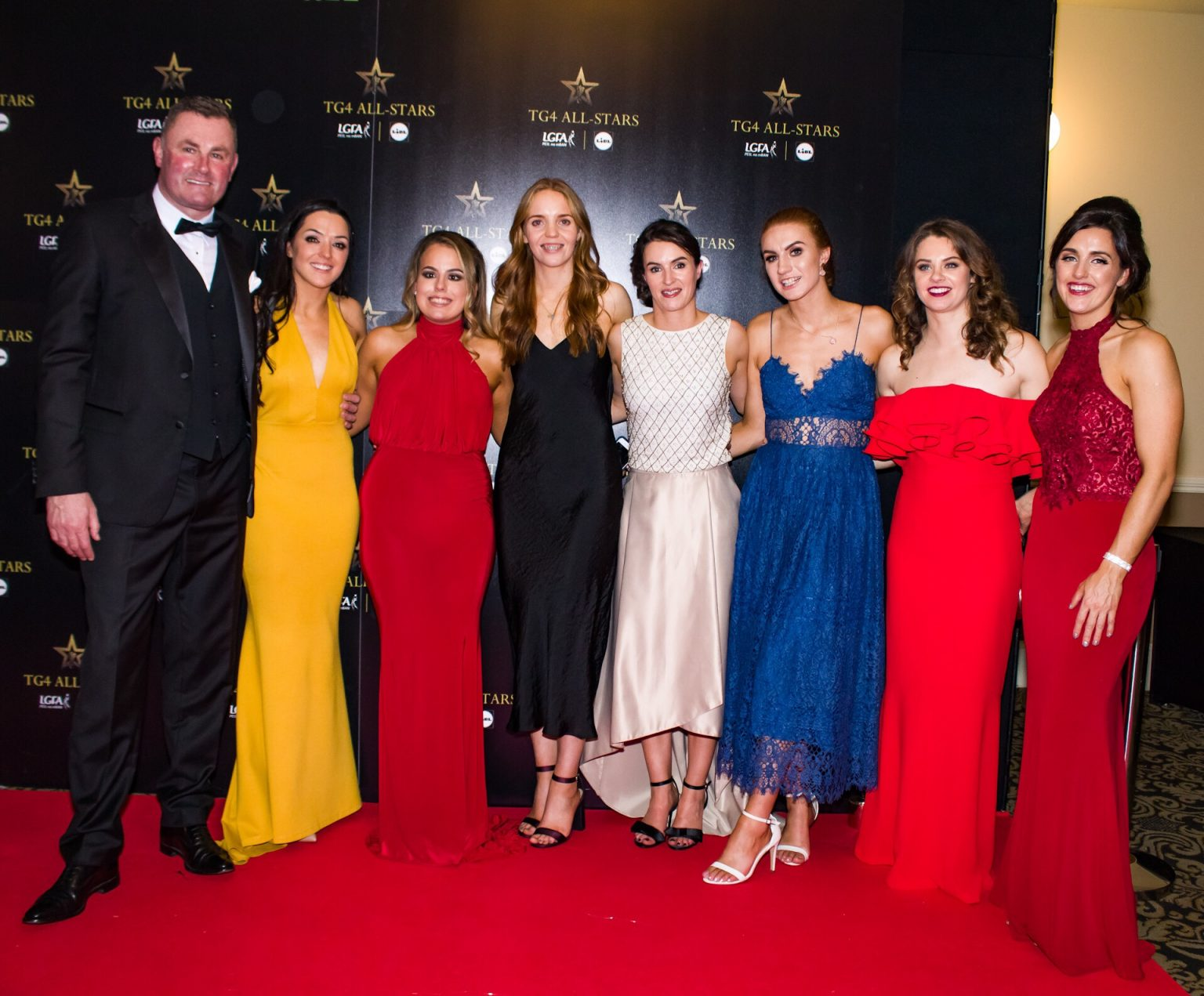 Dublin manager Mick Bohan in a black suit and bow tie with members of the Dublin ladies Football team.