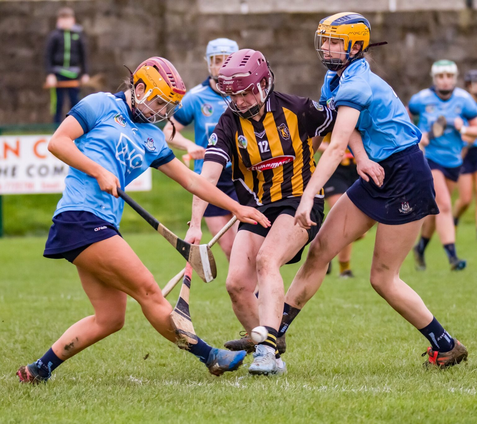 Two Dublin Camogie players in sky blue jerseys tackle a Kilkenny player in black and amber striped jersey