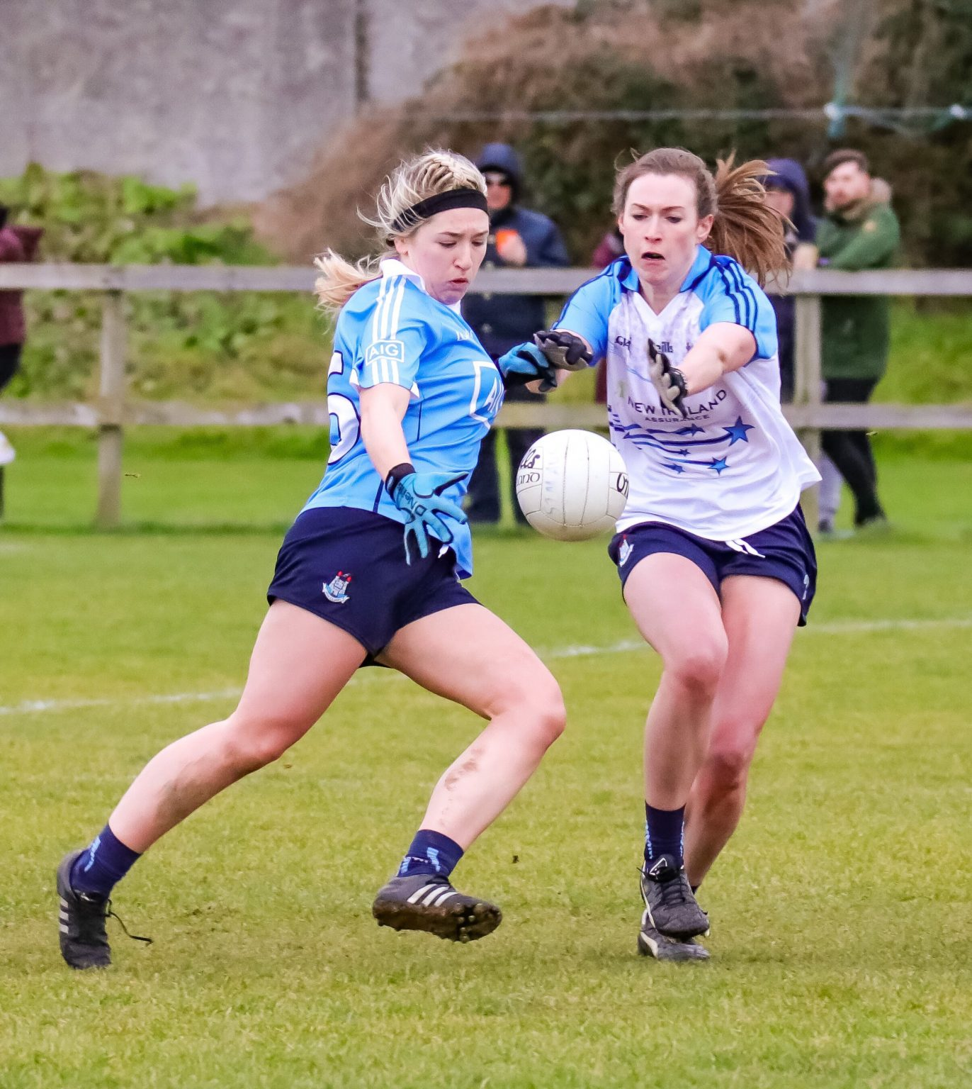 Two Dublin Ladies footballers one in a sky blue jersey and the other in a white jersey with blue sleeves battle for the ball at the Dublin LGFA Senior and Junior Dub Stars event