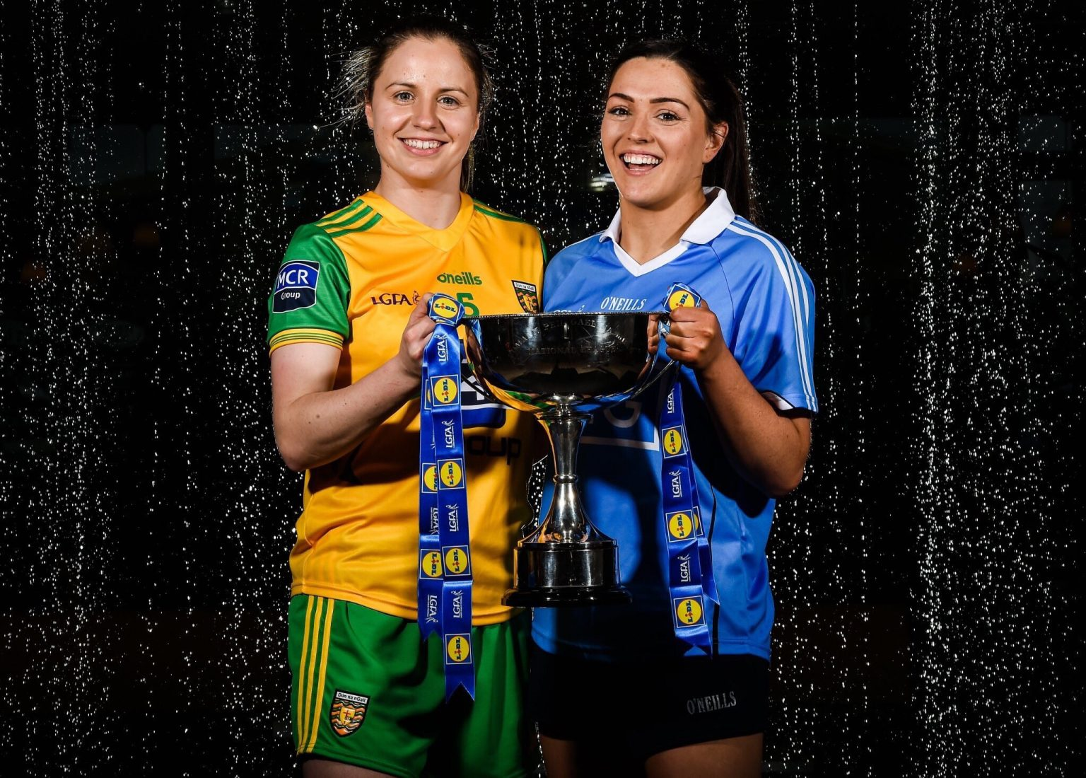 A Donegal Ladies Footballer in a yellow jersey with green sleeves holding the Division 1 National League Trophy with a Dublin player in a sky blue jersey to advertise Champions Dublin playing against Donegal in Croke Park