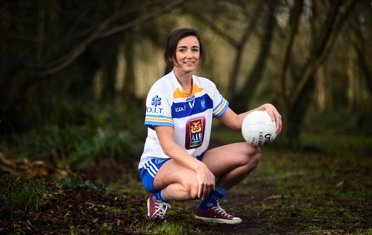 Dublin Ladies footballer Niamh McEvoy in a white jersey with blue and yellow stripes and a white football in a wood at the launch of the HEC Ladies Football Championships