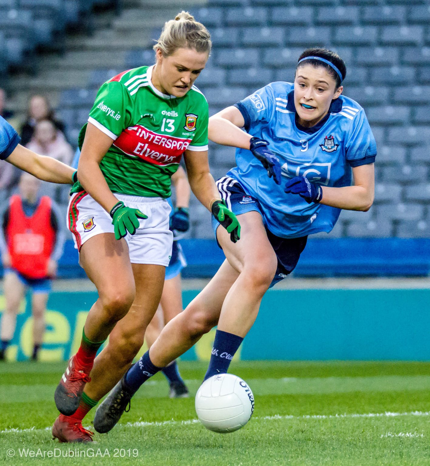 A dublin Ladies footballer in a sky blue jersey and navy shorts and a Mayo player in a green and red jersey and white shorts battle for the ball during their Lidl National Football League game.
