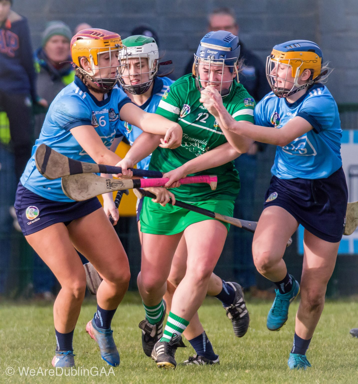 Two Dublin Camogie Players in sky blue jerseys and navy skorts tackle a Limerick player in a green Jersey and green skort in the Dublin Seniors League game in Division 1