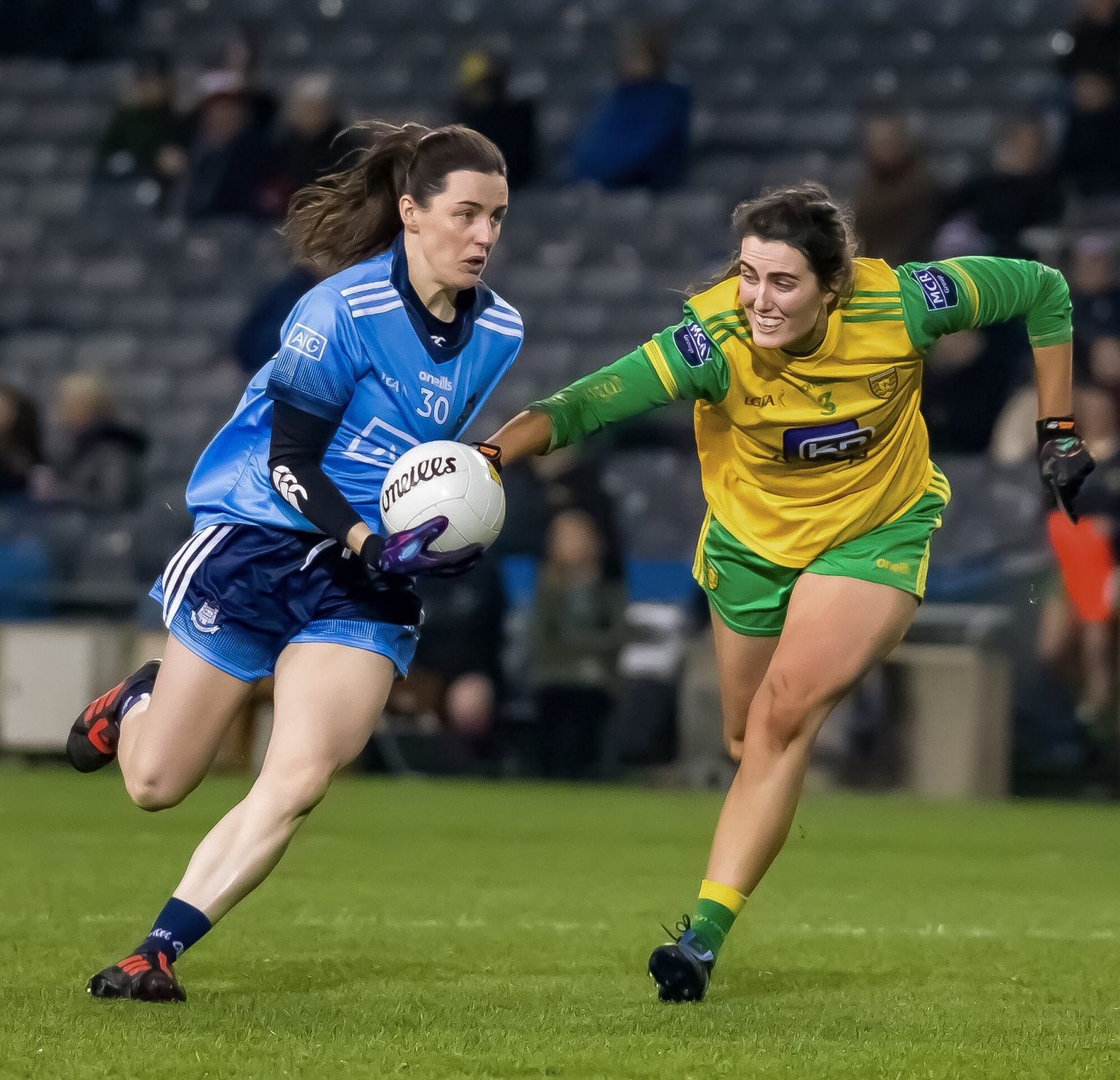 Dublin's Lyndsey Davey is a sky blue jersey and navy shorts evades the tackle of a Donegal player in a yellow jersey and green shorts in the Lidl Ladies National Football League