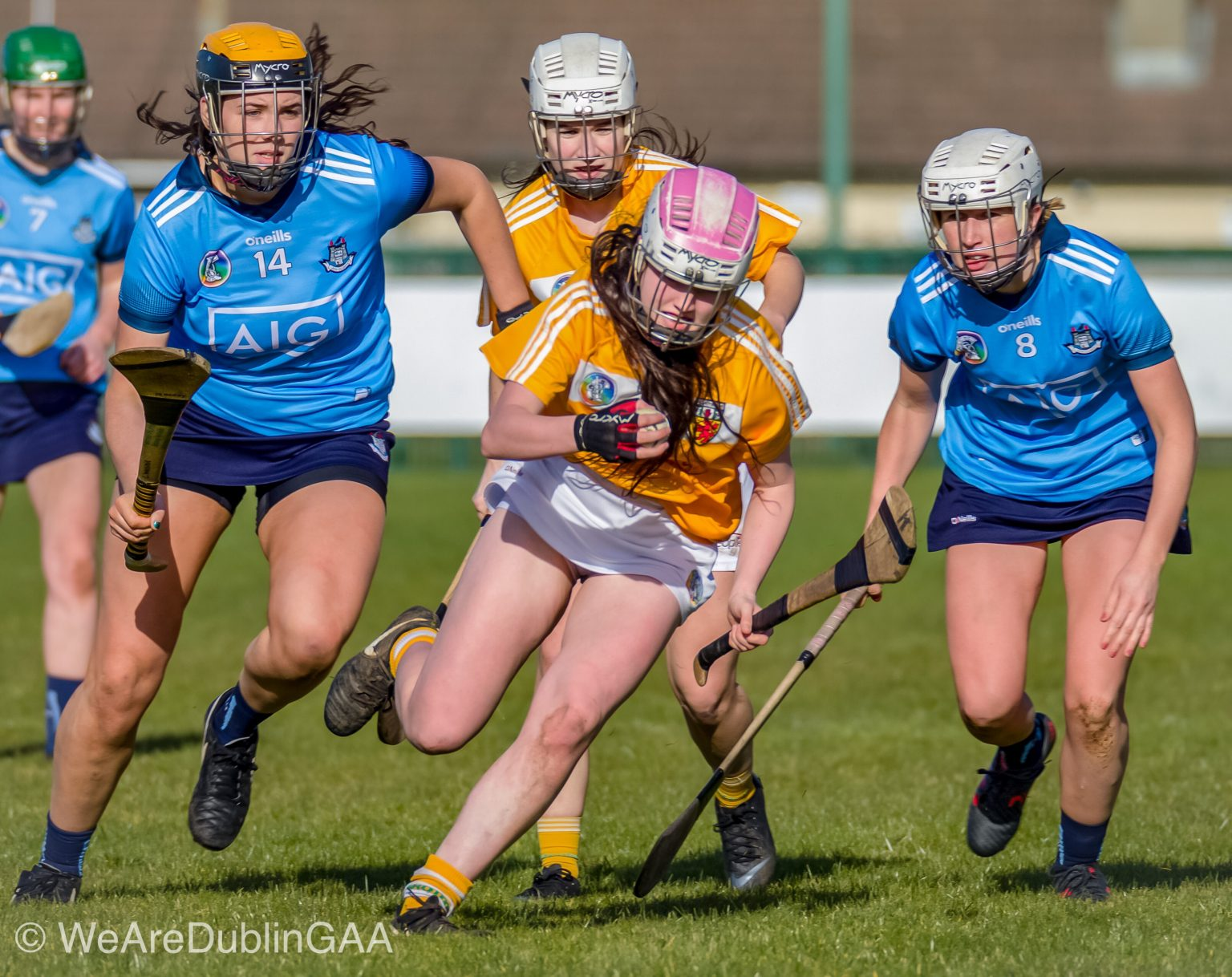 Two Dublin Camogie Players in sky blue jerseys and navy skorts tackle an Antrim player in yellow jersey and white shorts