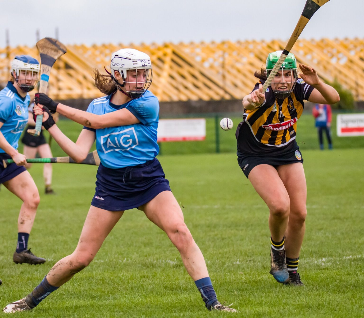 Dublin Senior Camogie Player in a sky blue jersey and navy skort striking the ball with her hurl