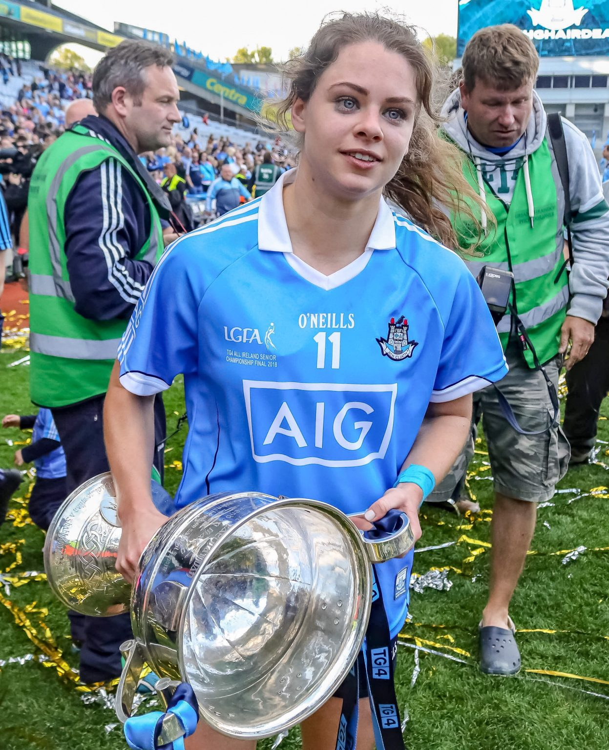 Dublin Ladies footballer Noelle Healy in a sky blue jersey holding the Brendan Martin Cup On the Croke Park pitch