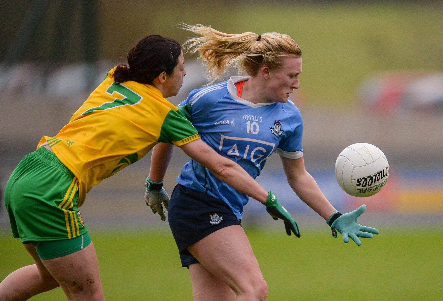 A Donegal Ladies footballer in a yellow jersey with green sleeves tackles a Dublin player in a sky blue jersey during the Lidl Ladies National Football League