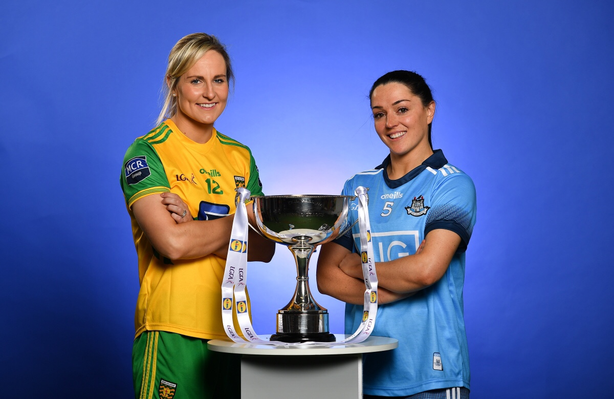 Donegal Ladies footballer in a yellow jersey with green sleeves and a Dublin Senior Ladies Football player in a sky blue jersey stand at a table with the league trophy
