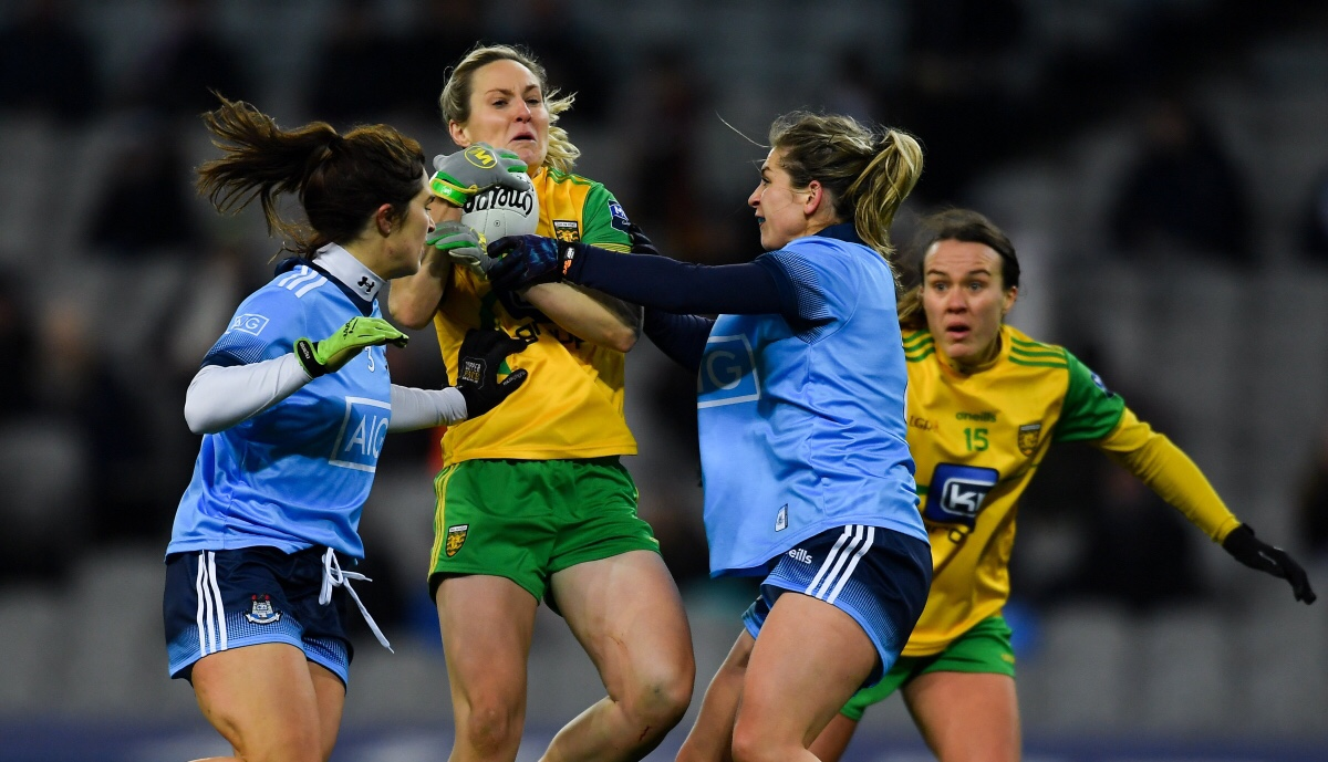 Donegal Ladies footballer in a yellow jersey with green sleeves is tackled by two Dublin players in sky blue jerseys