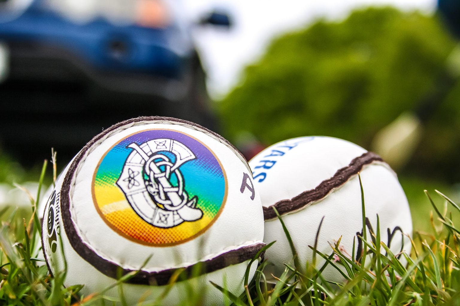 Two white sliotars on a grass pitch at the Dublin Camogie U14 Development Squad Training
