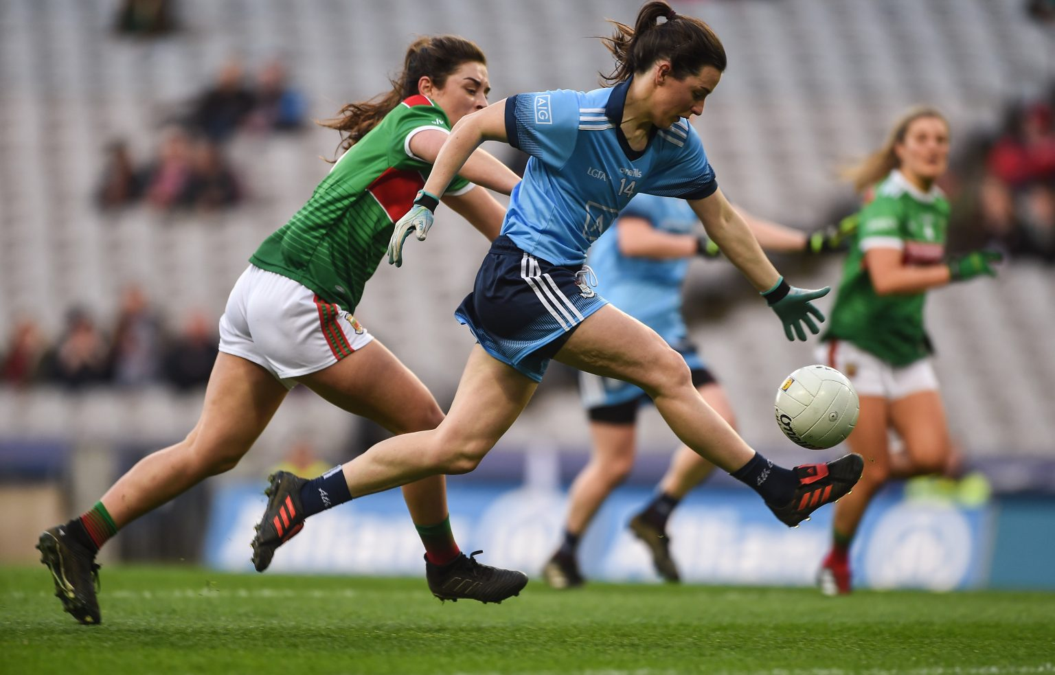 Dublin Ladies Footballer Lyndsey Davey in a sky blue jersey and navy shorts breaks away with the ball from a Mayo defender in a green and red jersey and white shorts