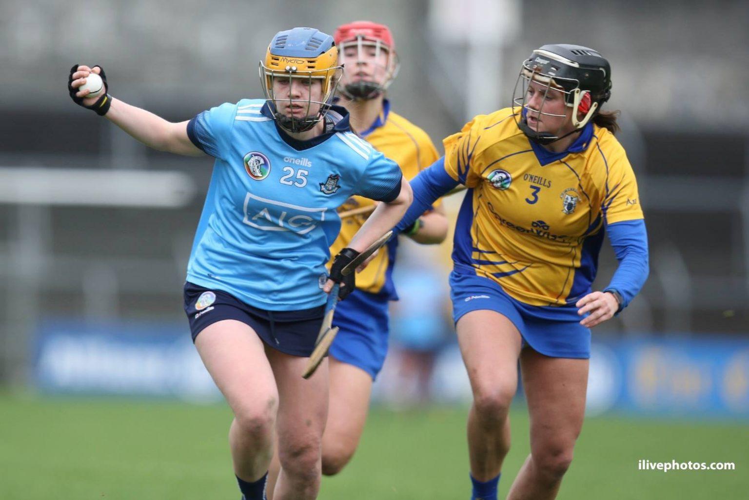 Dublin Senior Camogie Player in a sky blue jersey, navy skort and blue and yellow helmet breaks past a Clare player in a yellow and blue jersey, blue Skort and black helmet