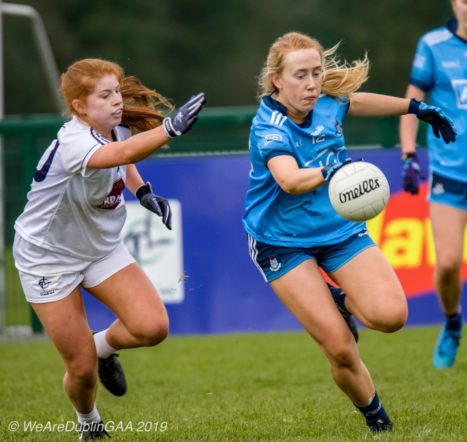 Dublin Ladies footballer in a sky blue jersey and navy shorts breaks away with the ball from a Kildare player in a white jersey and white shorts during Leinster Minor championship match which seen Dublin Relinquish the Leinster Minor title they have held since 2011