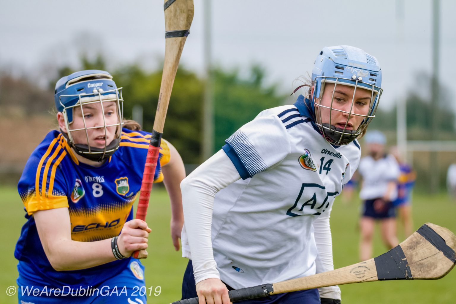 Dublin Camogie player in a white jersey with navy trim and light blue helmet breaks away from a Tipperary player in a dark blue jersey with yellow band across the middle and dark blue helmet during the championship fixture