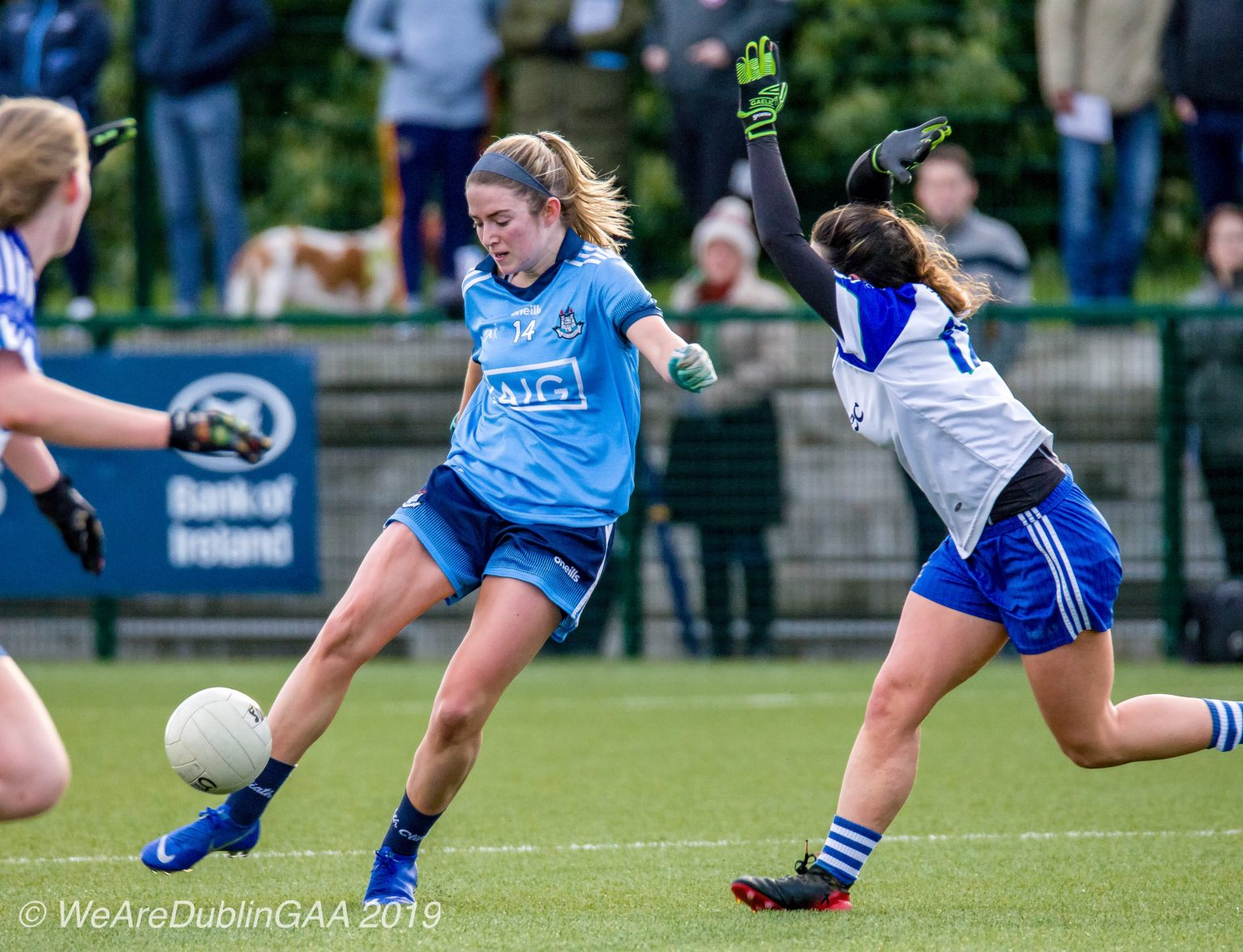 Dublin Ladies footballer in a sky blue jersey and navy shorts takes a shot at goal before a Monaghan player in a white jersey with blue sleeves and blue shorts during their Lidl Ladies NFL game