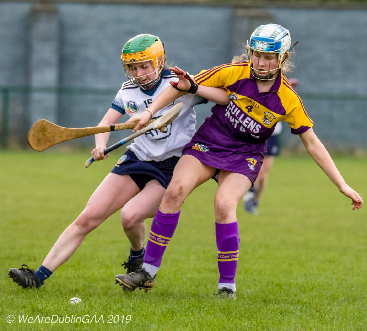 Dublin Camogie player in a white jersey, navy skort and yellow and green helmet battles for the ball with a Wexford player in purple jersey, purple skort and white and blue helmet