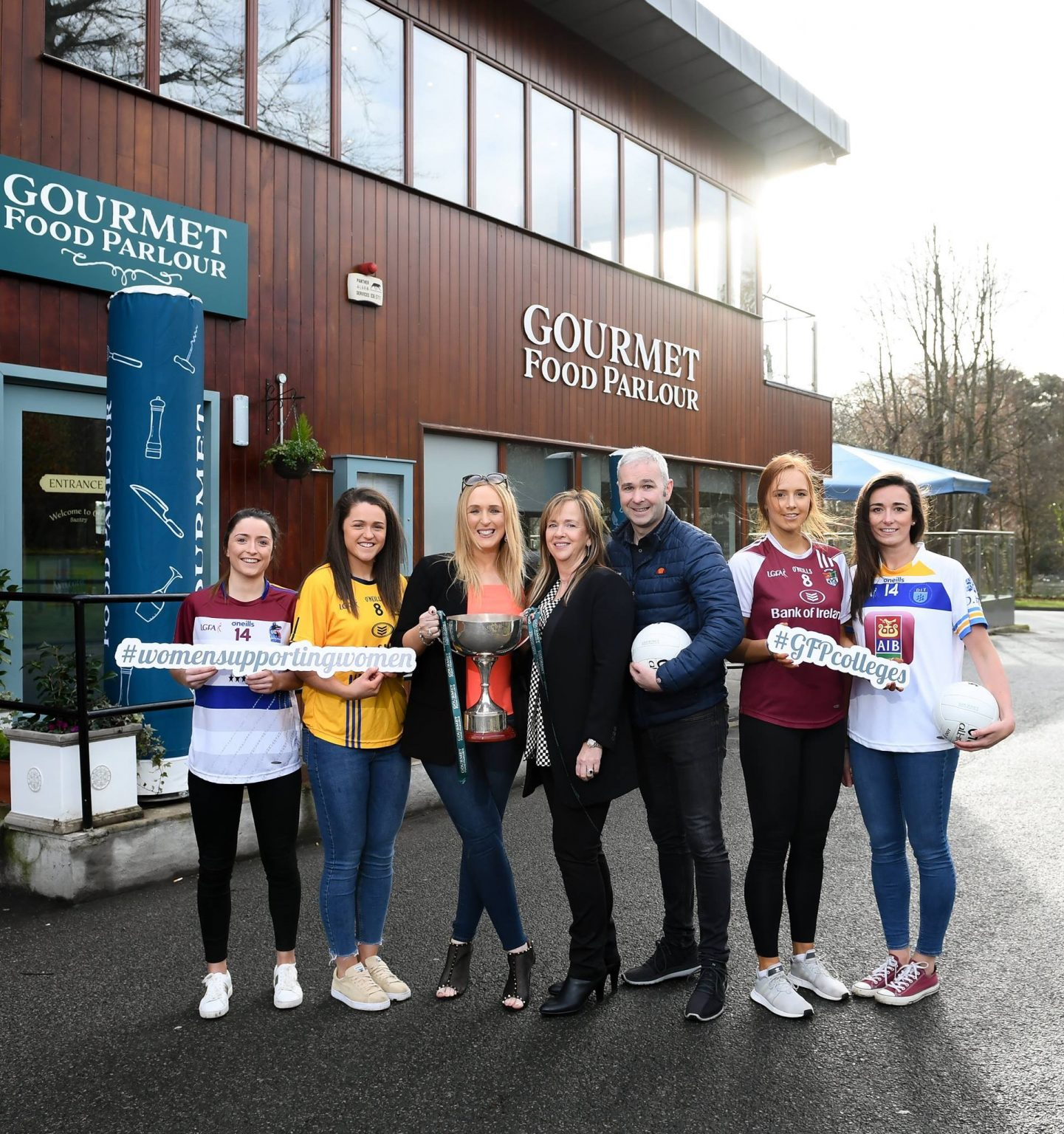 For Ladies Footballers two either side of the CEO of Ladies Gaelic Football Association and the owner of sponsors Gormet Food Parlour hold a cup to advertise the O'Connor Cup Semi Finals