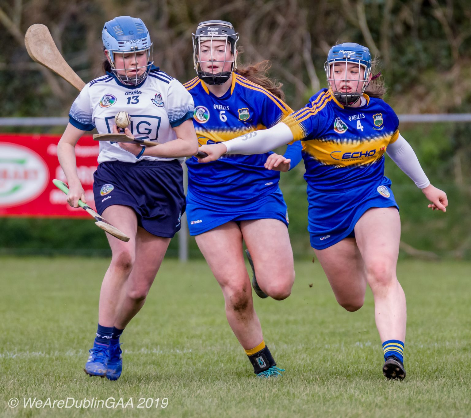 A Dublin Minor camogie player in a white jersey,navy skort and light blue helmet is tackled by two Tipperary players in dark blue jersey with yellow stripe across the front, dark blue Skort and blue helmets