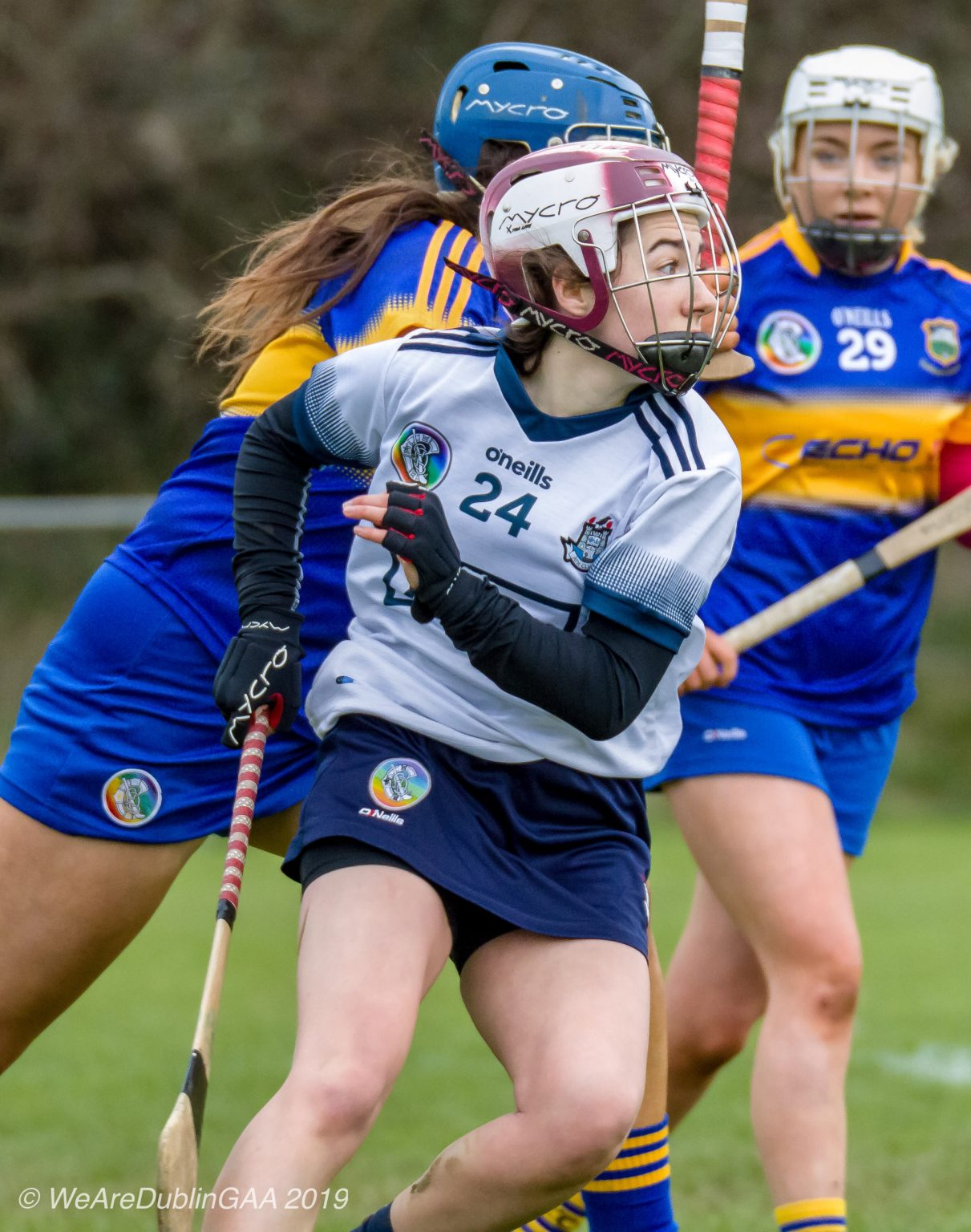 Dublin Minor Camogie Player In a White jersey with navy trim, navy skort and maroon and white helmet tries to evade a Tipperary player in a dark blue jersey with yellow band, dark blue skort and dark blue helmet during their Minor A Championship game