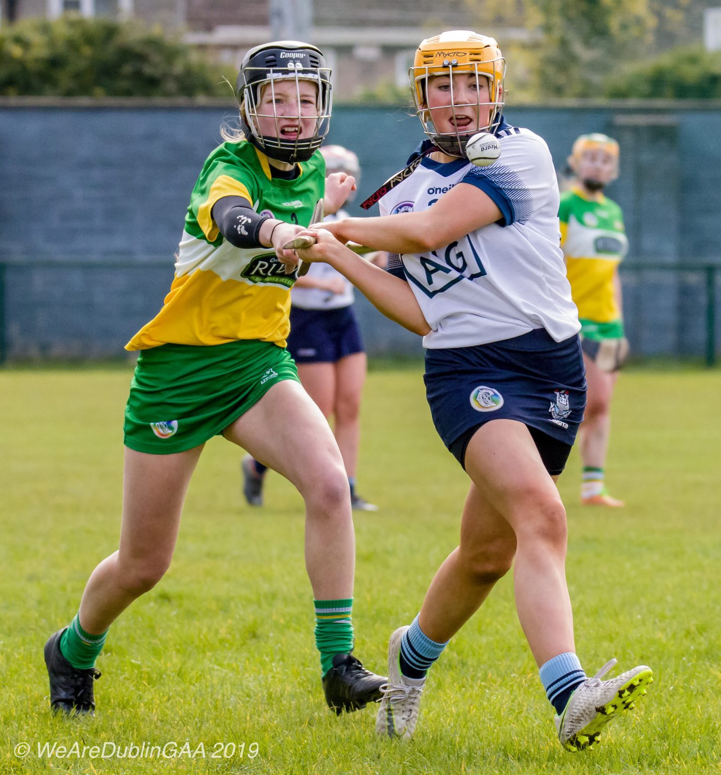 Dublin U16 Camogie Player In a White jersey with navy trim, navy skort and yellow helmet about to strike the ball as an Offaly player in a green,white and yellow jersey, green skort and black helmet tries to hook her hurl