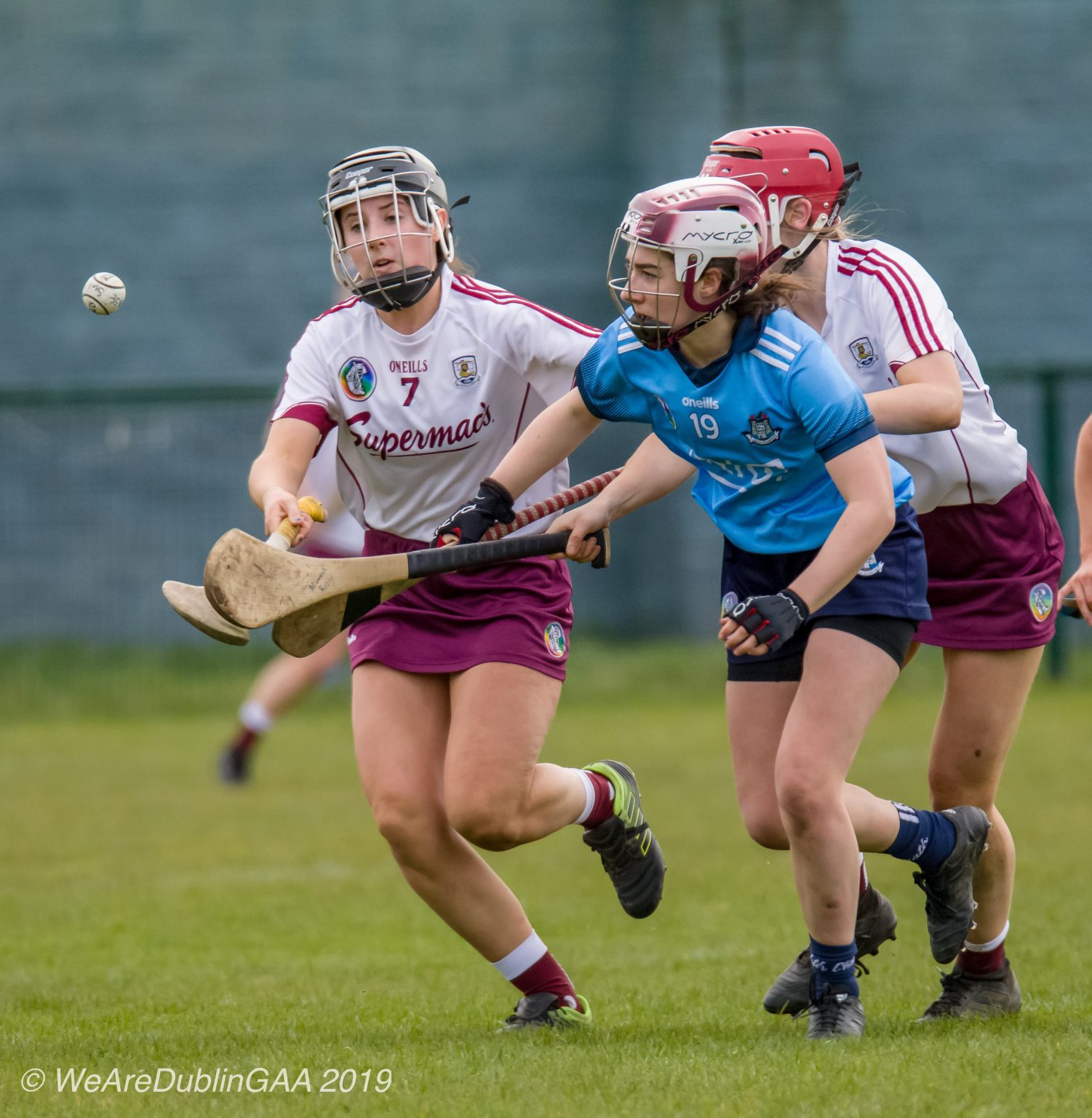 Dublin Minor Camogie player in a sky blue jersey, navy Skort and maroon and white helmet battles for the ball with two Galway Minors In white jerseys and maroon skorts