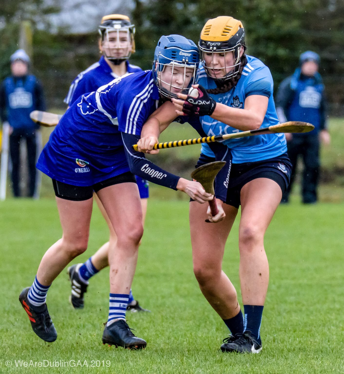 Dublin Camogie player on the right in a sky blue jersey, navy skort and yellow and black helmet is tackled by a Laois player in a dark blue jersey, dark blue skort and dark blue helmet during the Division 2 league game