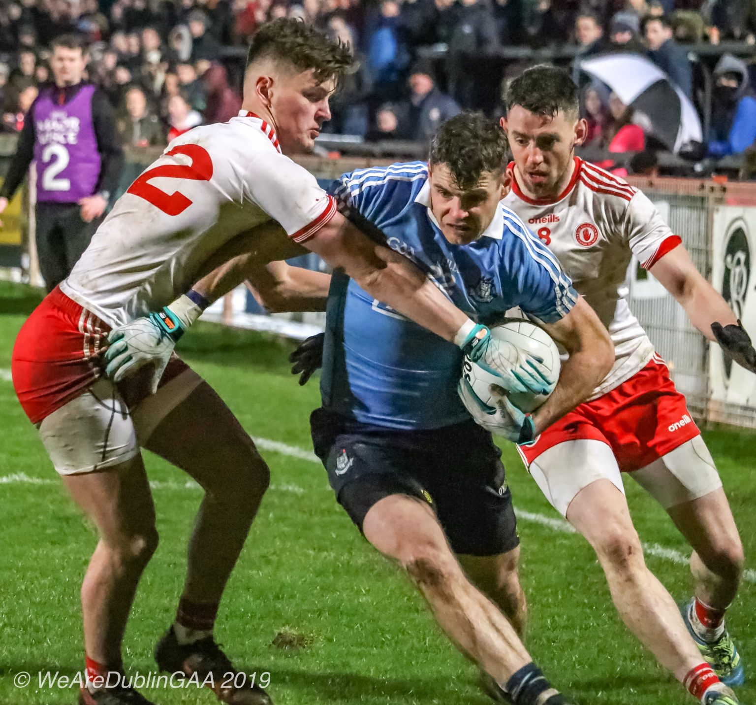 Dublin player in a sky blue jersey and navy shorts is tackled by two Tyrone players in white jerseys with red trim and red shorts during Dublin's League encounter with Tyrone