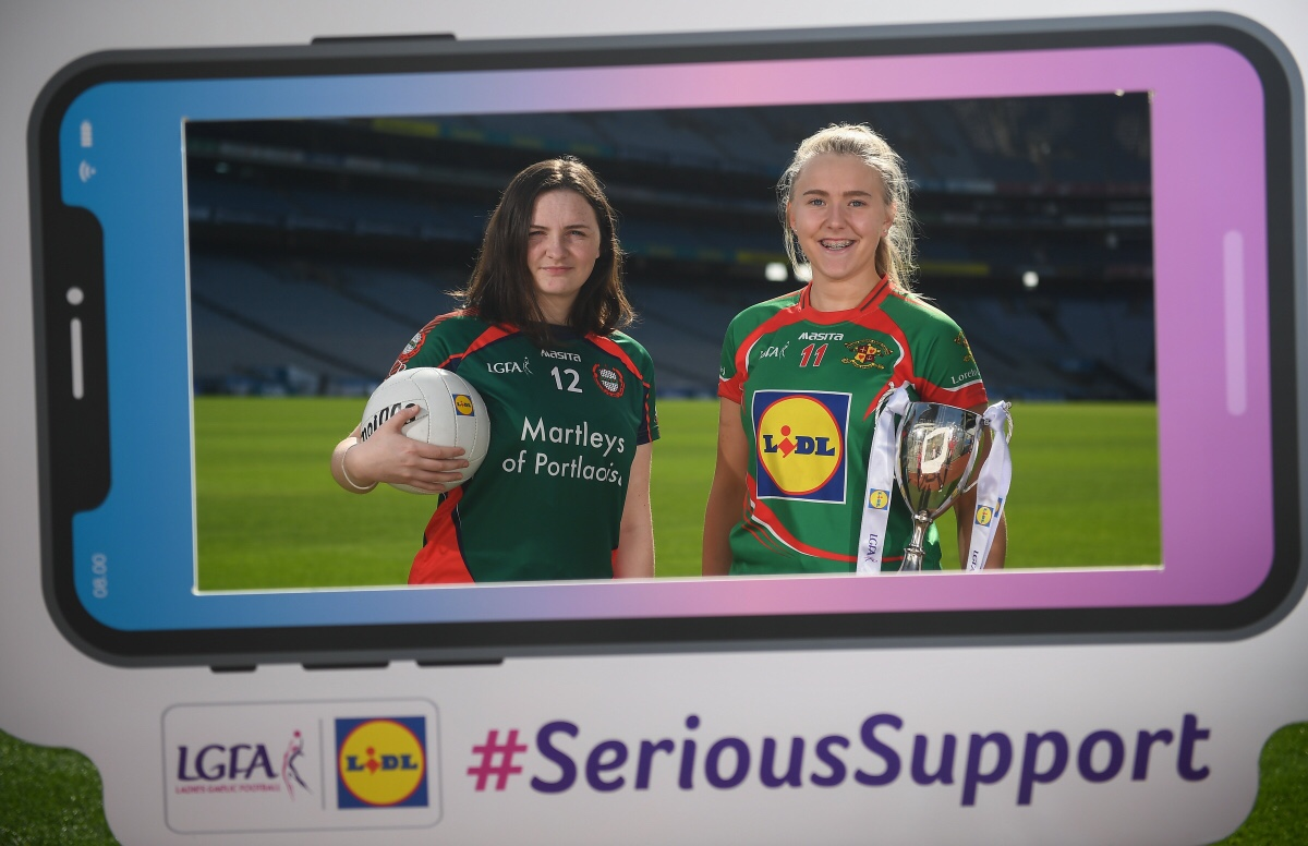Two Ladies Footballers In green and red jerseys one holding a ball and the other a trophy at the launch of the Post Primary Schools finals