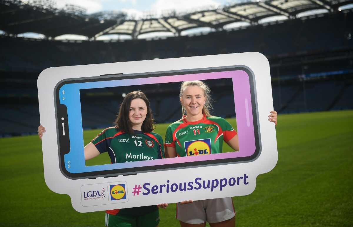 Two ladies Footballers in green and red jerseys hold a cut out of a mobile Phone with the words LGFA, Lidl and #SeriousSupport on it to advertise the PPS Senior Finals