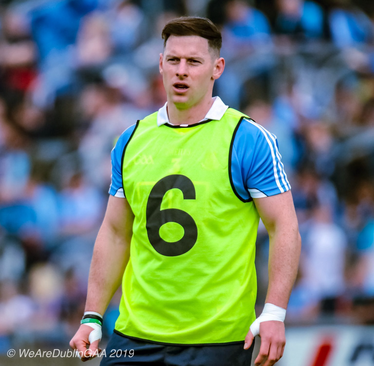 Dublin defender Philly McMahon in a sky blue jersey with a yellow bib over it with the number six on the front and navy shorts