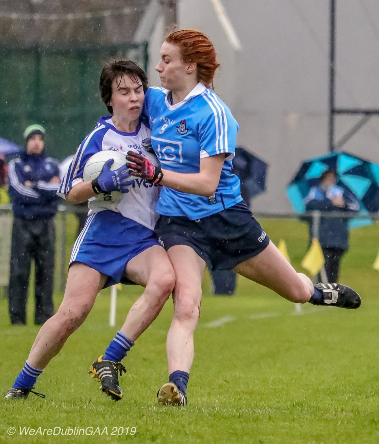 Dublin Ladies Footballer in a sky blue jersey and navy shorts tackled a Monaghan player in a white jersey with dark blue sleeves and dark blue shorts both sides face each other this weekend and the Inter County Update on the fixture venue is DCU