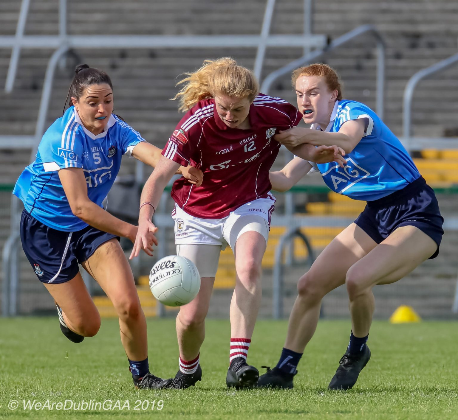 Two Dublin Ladies footballers in sky blue jerseys and navy shorts move in to tackle a Galway player in a maroon jersey and white shorts their NFL game will be live streamed on facebook