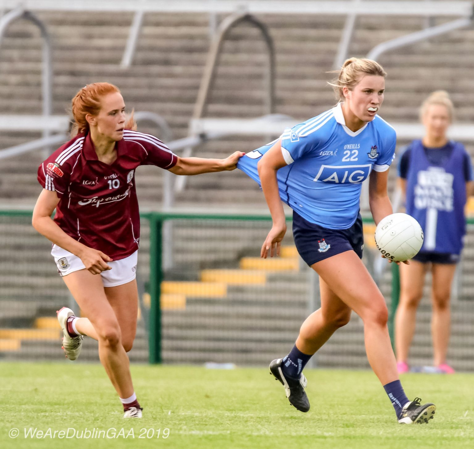A Dublin Senior Team Ladies footballer in a sky blue jersey and navy shorts tries to get away from a Galway player in a maroon jersey and white shorts who is holding onto her jersey