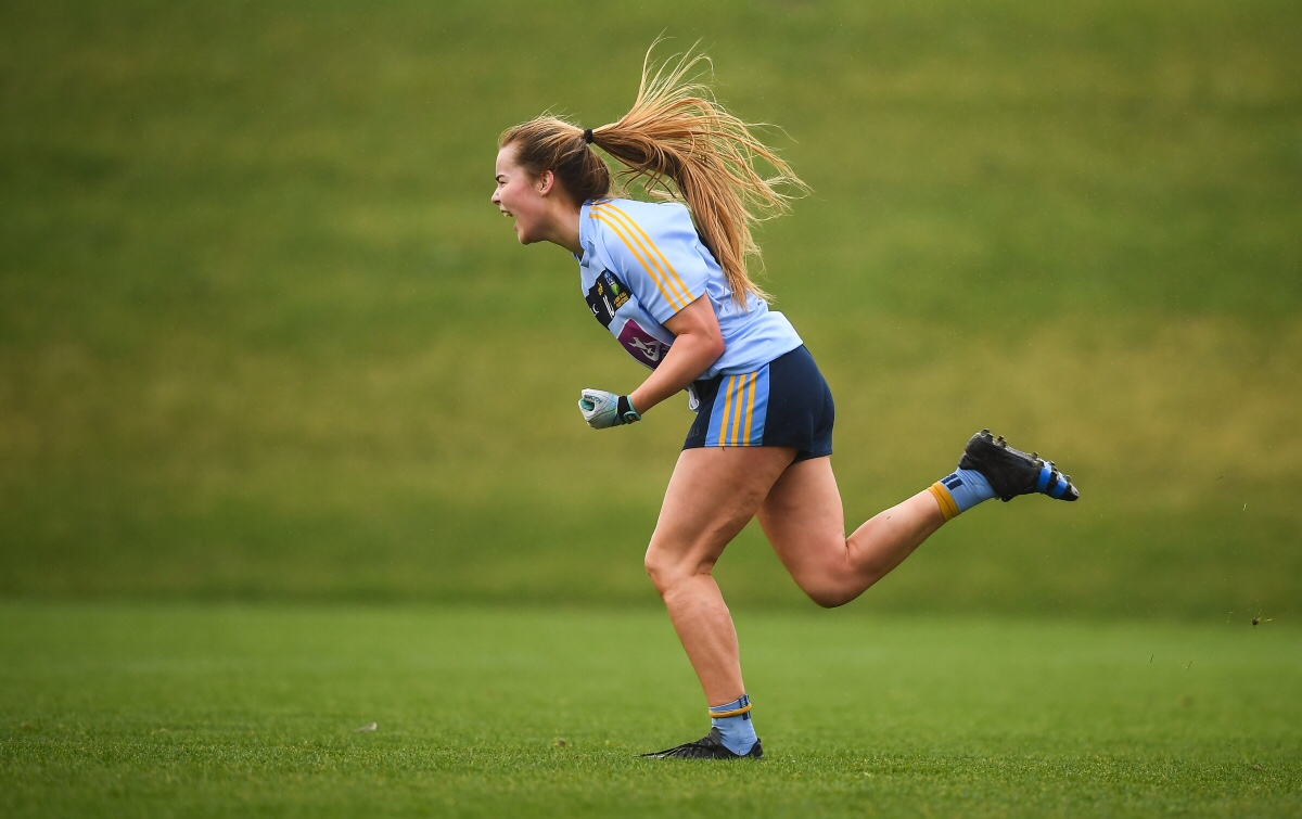 Andrea Murphy from UCD wearing a light blue jersey with yellow stripes on the sleeve and navy shorts with yellow and light blue stripes down the side runs away celebrating after scoring a late goal