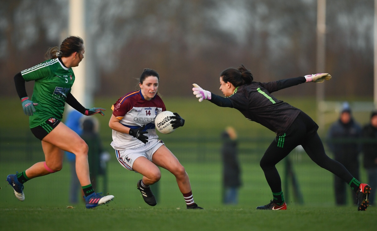 University of Limerick player in a white and maroon jersey and white shorts gets past the queens University goalkeeper in a black jersey and black shorts