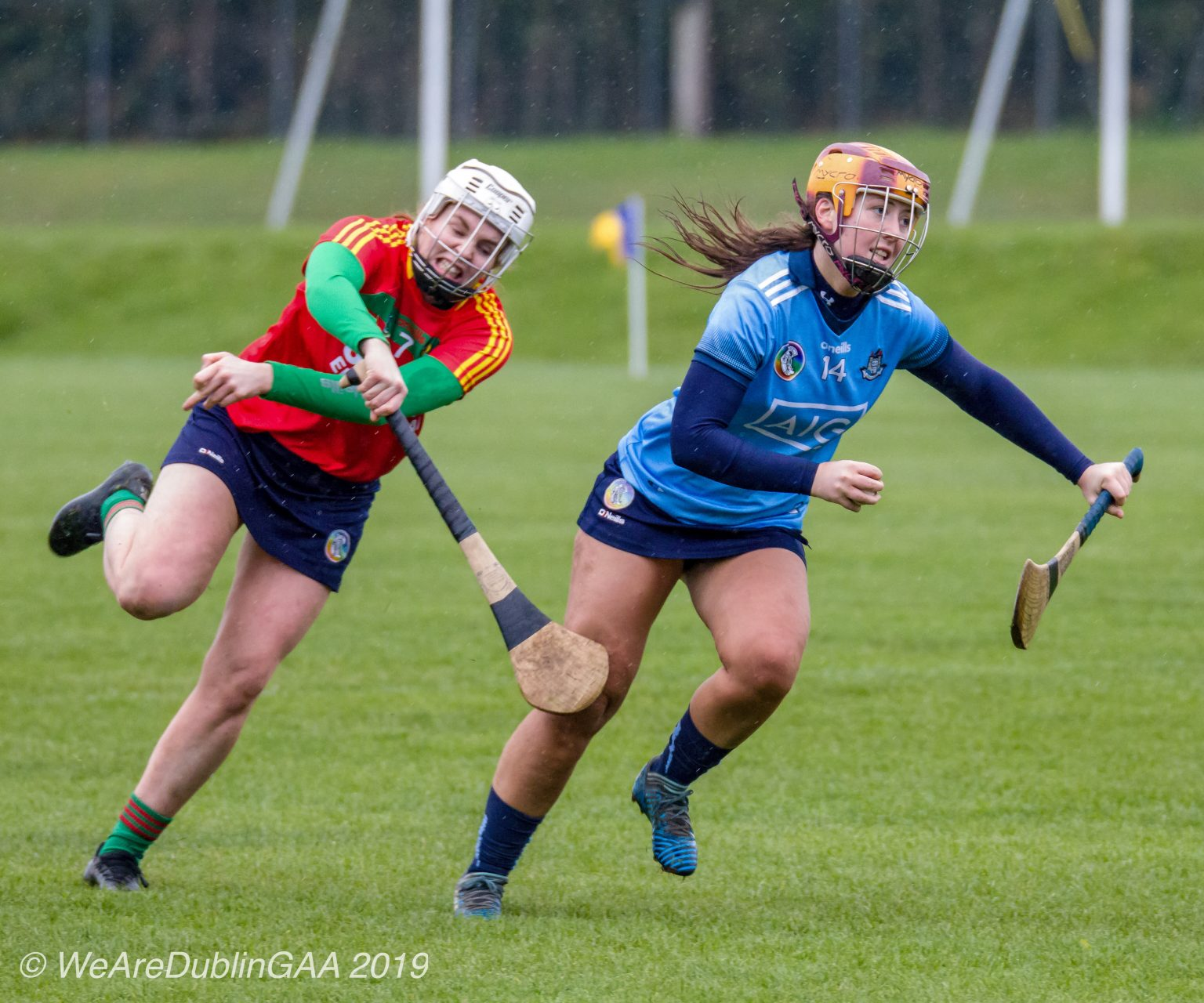 A Dublin Camogie player in a sky blue jersey, navy skort and yellow and wine helmets evades the tackle of a Carlow player in a red jersey, navy skort and white helmet during the relegation playoff game that Dublin won to retain their Division 2 status