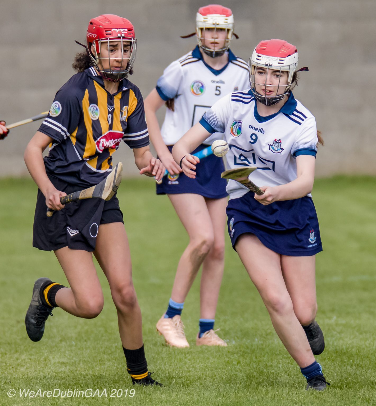 Dublin U16A Camogie Player In a White jersey with navy trim on the sleeves, navy collar and red and white helmet balances the ball on her hurl as she gets away from a kilkenny player in an Amber and black striped jersey, black skort and red helmet